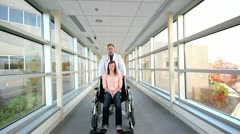 Doctor pushing wheel chair with young woman Stock Footage