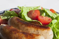 Stock Photo of sausages and salad with cherry tomatoes