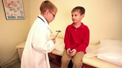 Young boy pretending to be doctor giving exam Stock Footage