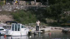 Fisherman in Cavtat harbor zoom out Stock Footage