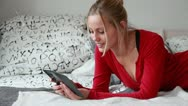 Stock Video Footage of Woman laying on bed using digital tablet.
