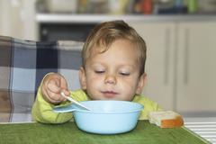 Serious baby is busy eating Stock Photos