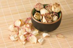 dried rosebuds in teacup and petals diagonal view - stock photo