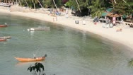 Stock Video Footage of Sunny beautiful beach with fishing boats and restaurants along the shore.