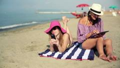 Two women with tablet computer and smartphone on the beach HD - stock footage