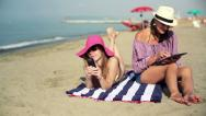 Stock Video Footage of Two women with tablet computer and smartphone on the beach HD
