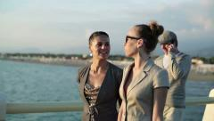Two happy glamour female friends walking on the pier, steadicam shot HD Stock Footage