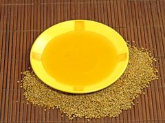 honey in yellow plate and flower pollen. - stock photo