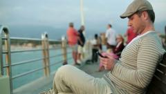 Happy young man using smartphone on pier, steadicam shot HD Stock Footage