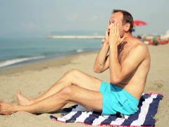 Man on beach applying sun block lotion on his face NTSC Stock Footage