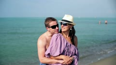 Young couple standing on the beach and talking Stock Footage