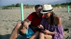 Couple at the beach using electronic tablet Stock Footage