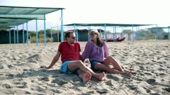 Happy couple sitting on beach and talking Stock Footage