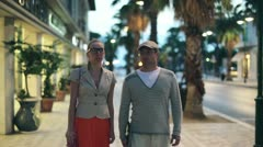 Young couple walking along shopping arcade in the evening - stock footage