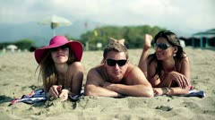 Three tanned young people lying on sand and looking at camera with toothy smiles - stock footage