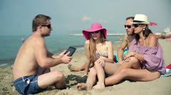 Group of friends taking photo with tablet computer on the beach Stock Footage