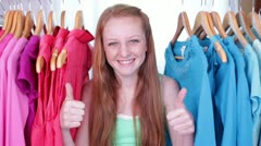 Cute Teen/Tween Gives Thumbs Up Sign from Clothes Rack Stock Footage