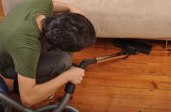 Stock Photo of young man with vacuum cleaner