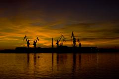 Lovely sunset and the shipyard cranes Stock Photos