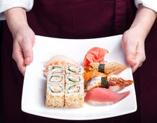 Chief cook holding plate with sushi Stock Photos