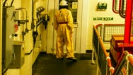 Nuclear Power Station Yellow Suited Worker and Fuel Rod Equipment Stock Footage