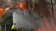 Fireman spraying water on a building consumed by fire Stock Footage