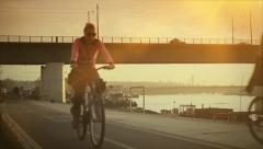 Couple riding bikes on river bank at the sunset Stock Footage