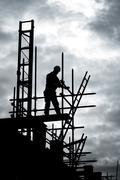 Builder on scaffold building site Stock Photos