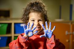 happy little girl painting with hands in kindergarten - stock photo