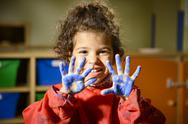 Stock Photo of happy little girl painting with hands in kindergarten