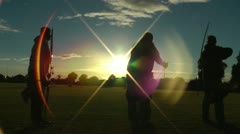 Archers in silhouette with lens flare, recurve, compound and longbow - stock footage