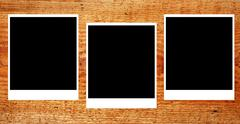 Set of three old blank polaroids frames lying on a wood surface Stock Photos