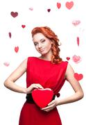 Smiling red-haired girl holding red heart Stock Photos