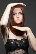 Stock Photo of young red-haired woman with rised hands
