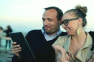 Happy couple chatting with tablet computer, outdoors Stock Footage