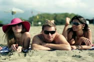 Three tanned young people lying on sand and looking at camera with toothy smiles Stock Footage