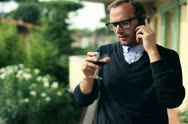 Young man standing with cellphone drinking wine on the balcony, steadicam shot Stock Footage