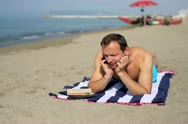Man relaxing on the beach and talking on a cell phone Stock Footage