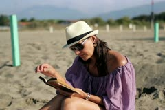 Attractive woman sitting on the beach and reading book Stock Footage