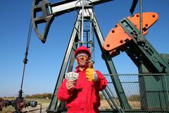 Happy Oil Worker with Money and Pump Jack Stock Photos