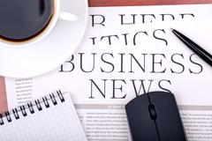 Business newspaper, notebook, mouse and cup of coffee Stock Photos