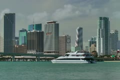 Yacht passes Miami downtown skyline seen from across Biscayne bay Stock Footage