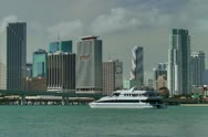 Stock Video Footage of Yacht passes Miami downtown skyline seen from across Biscayne bay