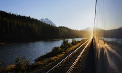 Train Alongside River And Mountains At Sunset Stock Photos