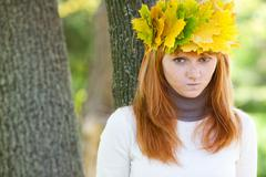 portrait of a beautiful young redhead teenager woman in a wreath of maple lea - stock photo