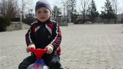 Little beautiful boy rides on a toy car Stock Footage