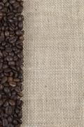 Burlap background with coffee beans. Stock Photos