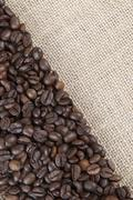 burlap background with coffee beans. - stock photo
