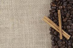 coffee beans and cinnamon on a burlap. - stock photo