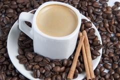 Cup of coffe over coffee beans. Stock Photos